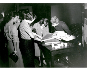 This photo from 1957-1958 shows women looking at a Western Players scrapbook, now in our collections, that was already 23 years old. It is now 80 years old.