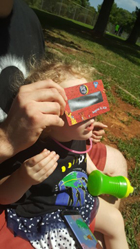 Young child looking through solar viewer